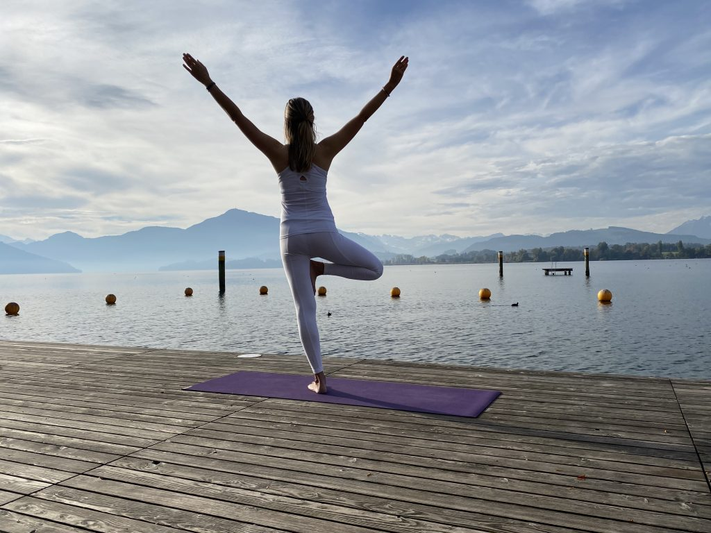 A woman doing Yoga by a large water body.